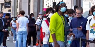 People queuing outside retail outlet wearing masks