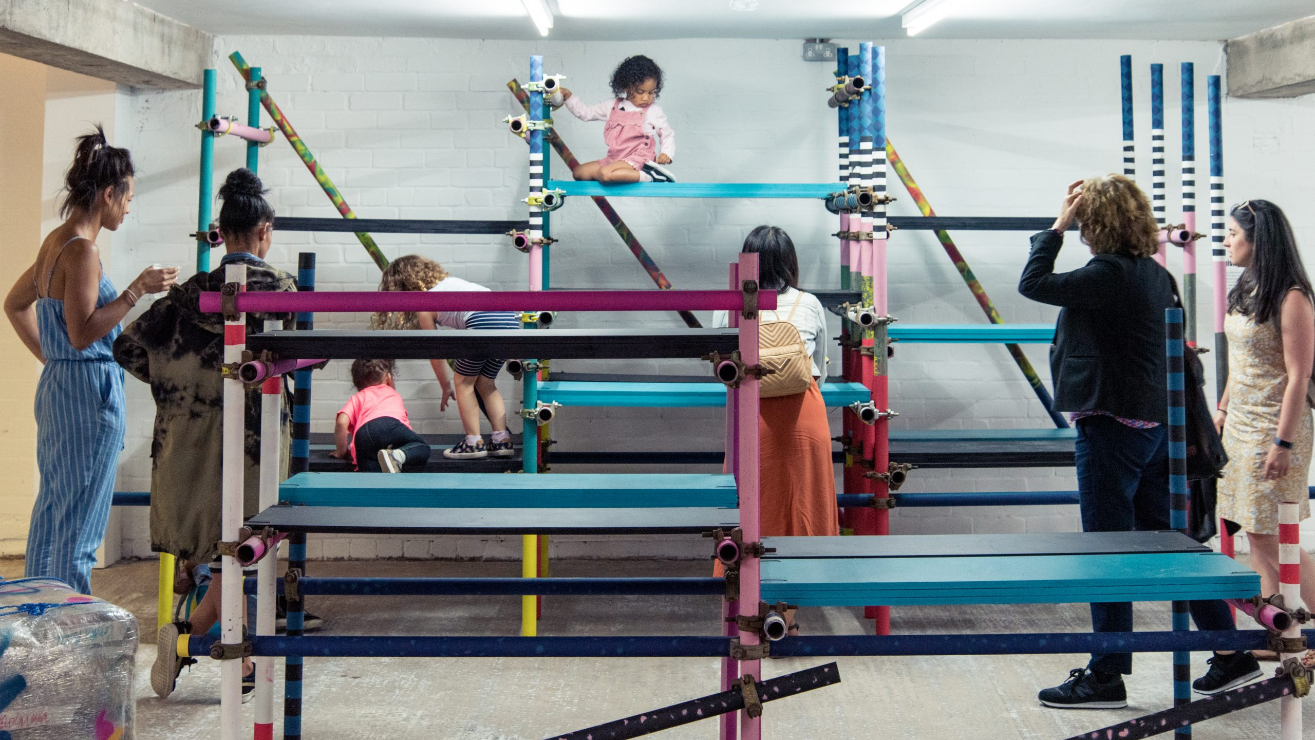 Children and adults climb on installlation in a gallery