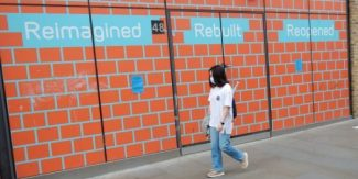 Woman walking next to reimagined rebuilt reopened sign